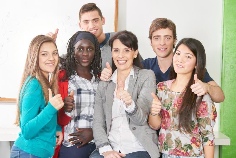 Mellan skilda raser grupp av studenter med läraren arkivbilder