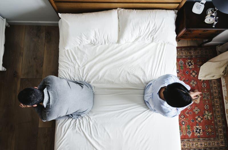 Mellan skilda raser par som tillbaka sitter för att dra tillbaka på sängen royaltyfri foto