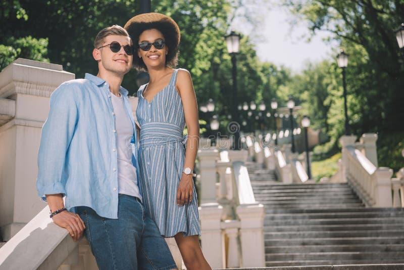 mellan skilda raser stilfulla par i solglasögonanseende arkivfoton