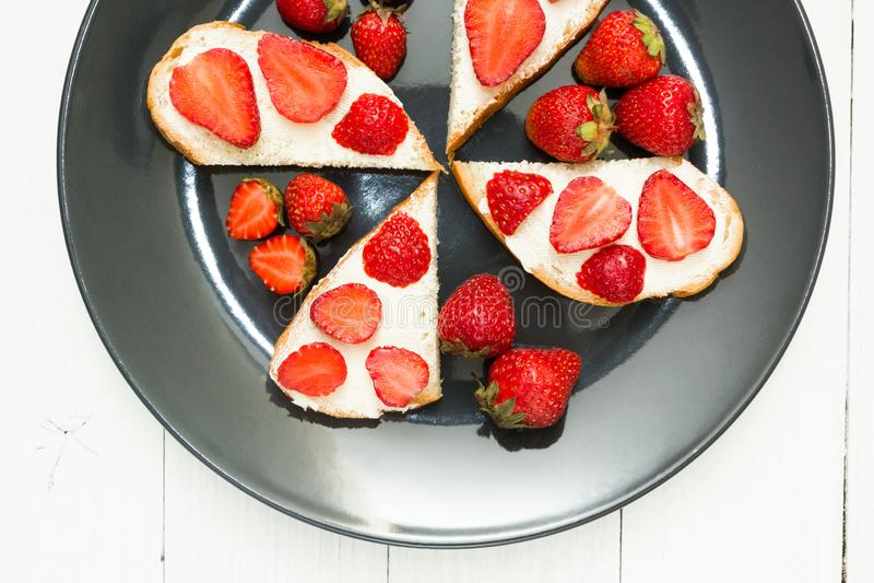 Mellanmål av nya smörgåsar med jordgubbar på en vit tabell Sund frukost, bästa sikt arkivfoto