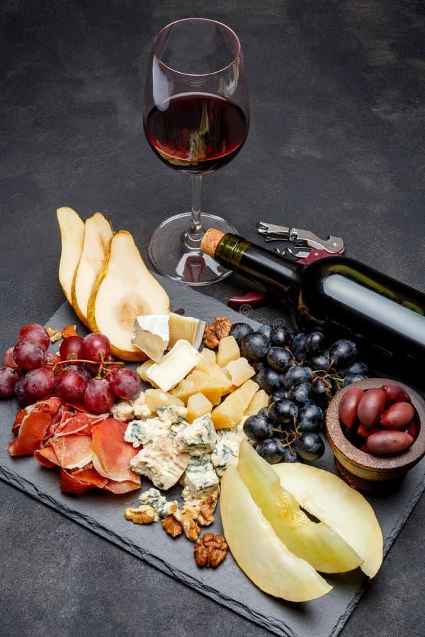 Mellanmål för köttplattaantipasti - Prosciuttoskinka, ädelost, melon, druvor, oliv royaltyfria foton