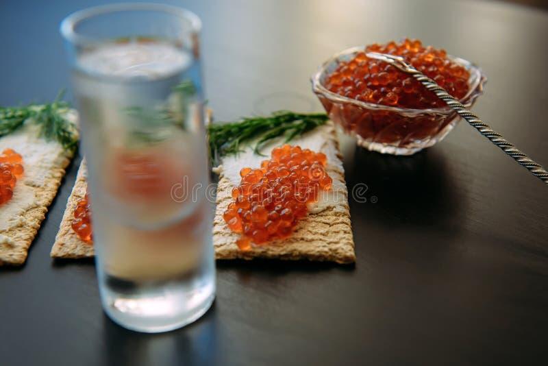 Mellanmål med den röda kaviaren och exponeringsglas av kall vodka på svart träbakgrund Andar och traditionell startknapp royaltyfri bild