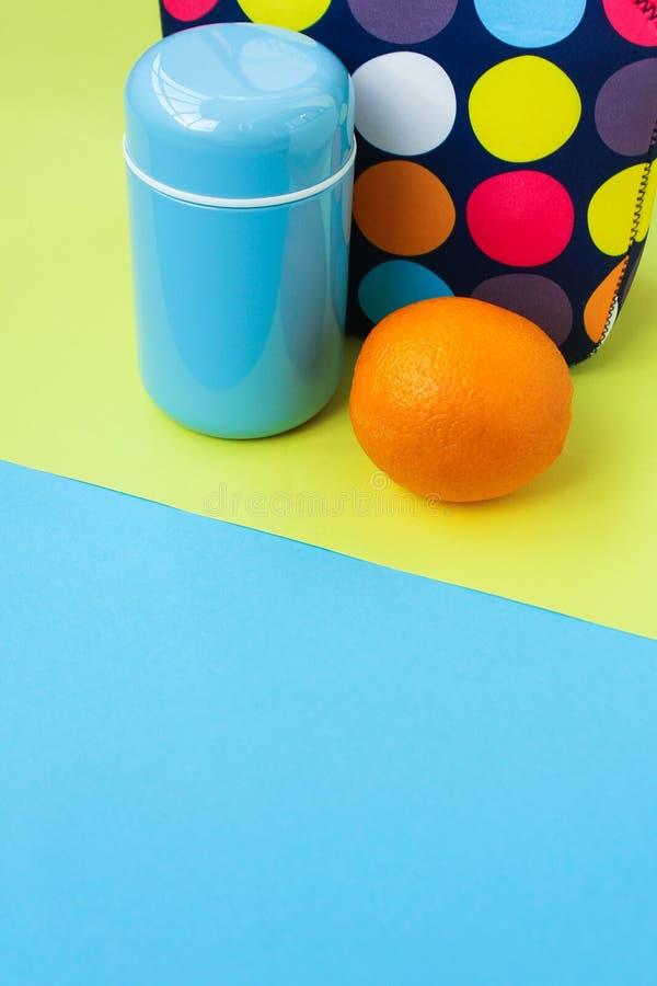 Mellanmål på ett avbrott med en lunchbox mångfärgad handväska, blå termos som är orange royaltyfri foto