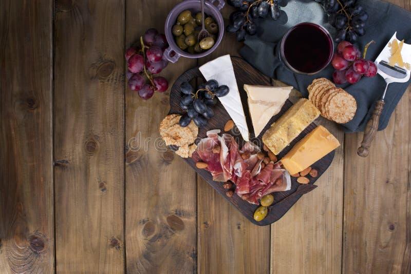 Mellanmål till vin Skinka, olik ost, oliv, druvor, bröd och rött vin i ett exponeringsglas spelrum med lampa Itian mat placera te arkivfoton