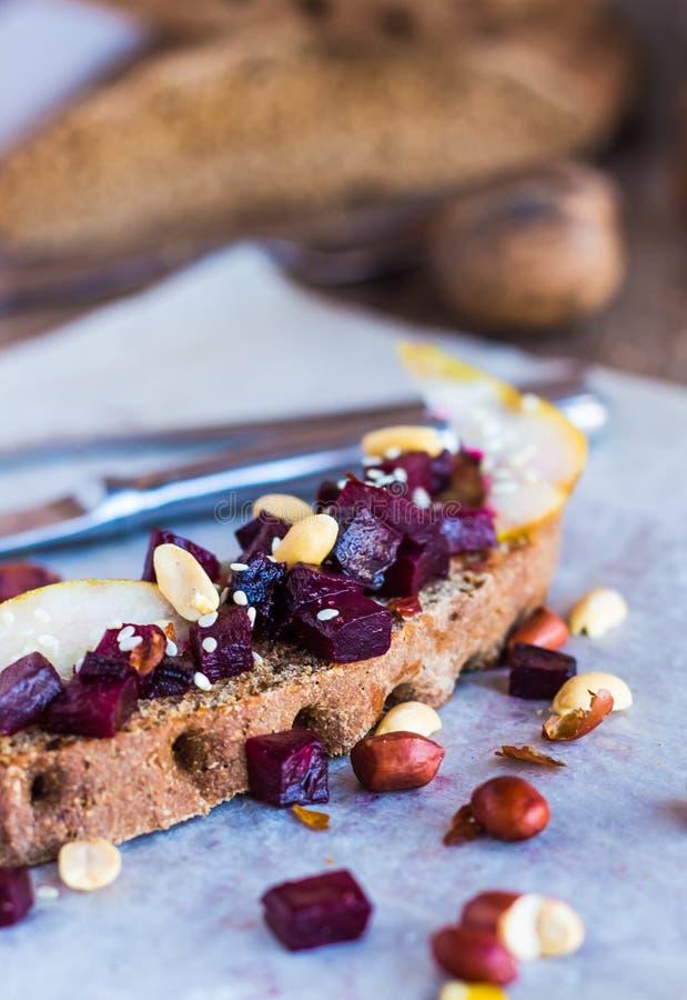 Mellanmålsmörgås med beta, valnötter och caramelized päron royaltyfria bilder