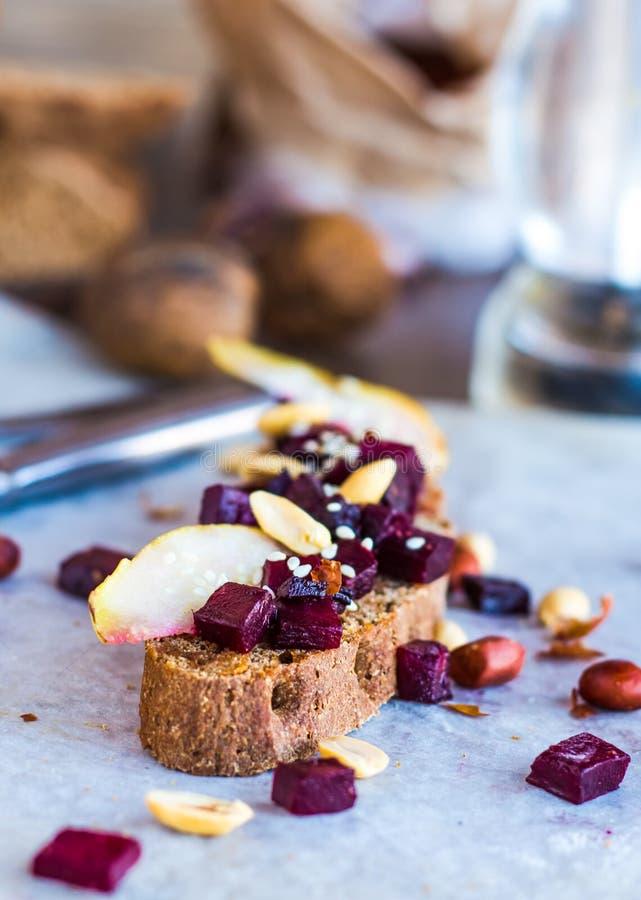 Mellanmålsmörgås med beta, valnötter och caramelized päron arkivfoton