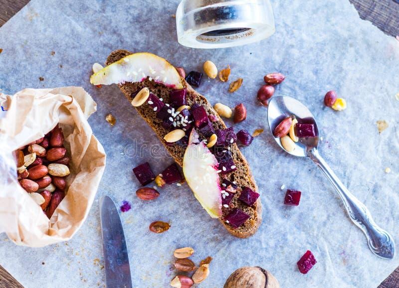 Mellanmålsmörgås med beta, valnötter och caramelized päron arkivbild