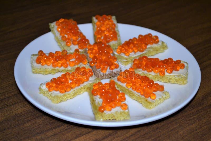 Mellanmålsmörgåsar med den röda kaviaren royaltyfria bilder