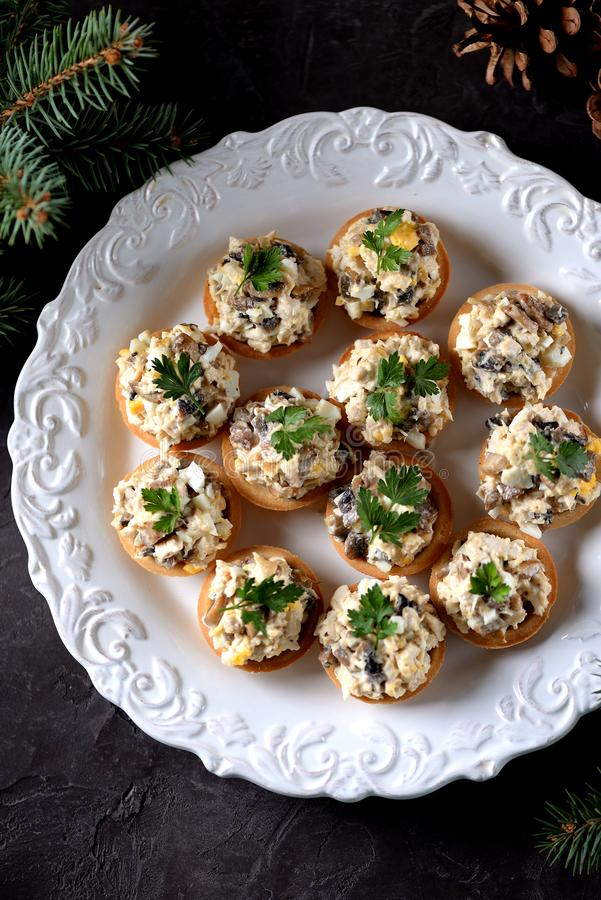 Mellanmåltartlets med kokt höna, stekte champinjoner och löken med ägget och majonnäs royaltyfri bild