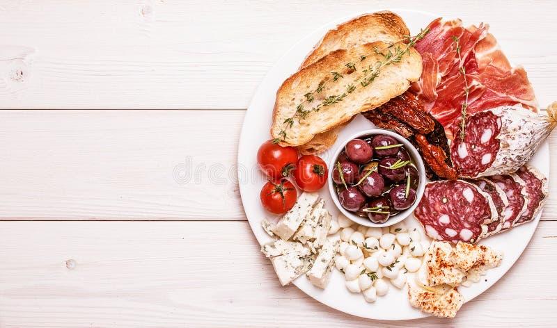 Mellanmåluppsättning Variation av ost och kött, oliv, tomater på vit royaltyfri fotografi
