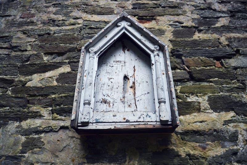 Mellanrumsträtappningljus - blå anslagstavla med den dekorativa ramen som hänger på stenväggen arkivfoto