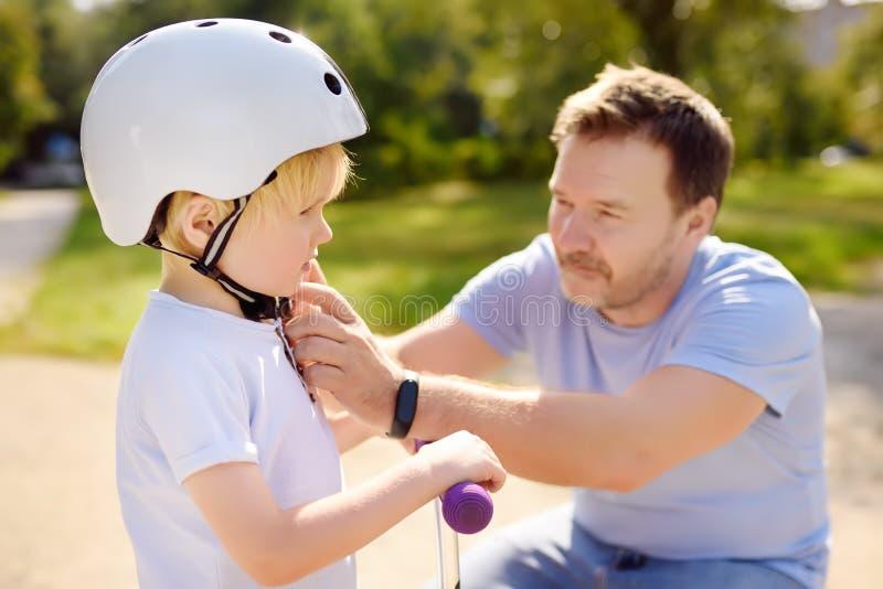 Mellersta ålderfader som hjälper hans lilla son att sätta hans hjälm Aktiv pys som rider en sparkcykel royaltyfri fotografi