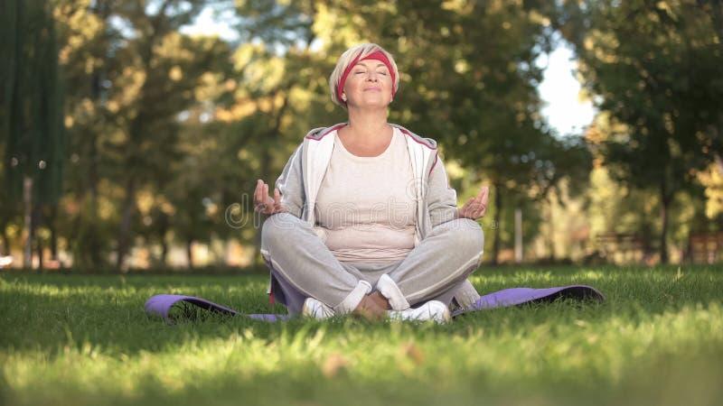 Mellersta ålderkvinna som andas och mediterar djupt sammanträde i lotusblommaposition royaltyfri foto