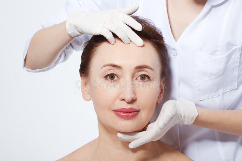 Mellersta ålderkvinna som får brunnsortbehandling Närbild av en ung kvinna som får Spa behandling Anti-åldras botox och collagen  arkivfoton