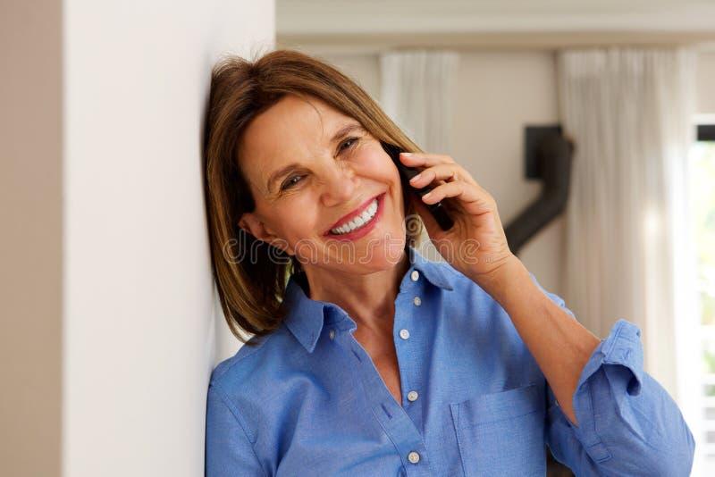 Mellersta ålderkvinnabenägenhet mot väggen och samtal på mobiltelefonen arkivbild