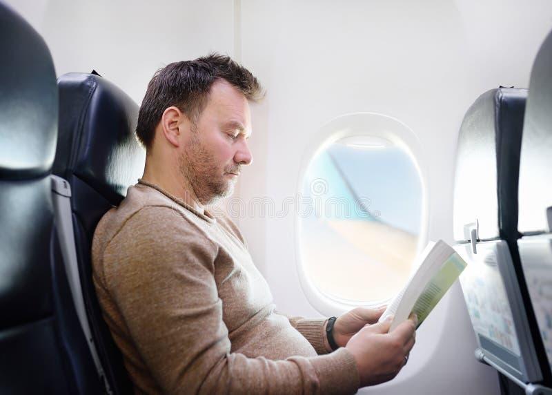 Mellersta åldermanresande vid ett flygplan och en läsning en bok under flyget begrepp isolerad trans royaltyfria foton