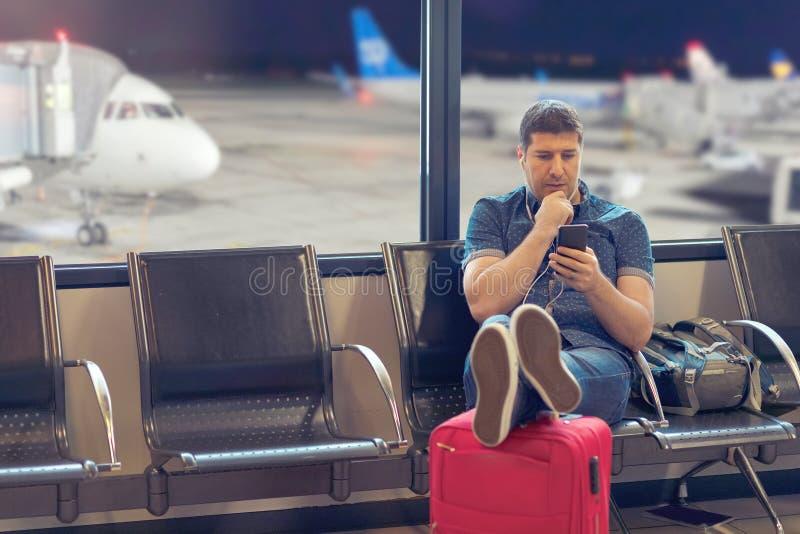 Mellersta åldermanturist som använder den smarta telefonen i flygplatsterminalen som ser försenade scheman för flyg royaltyfri fotografi