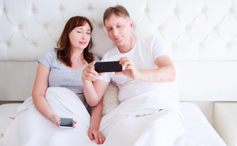 Mellersta ålderpar, kvinna och man som använder smartphonen på sovrummet Ultra brett hem- skott arkivfoto