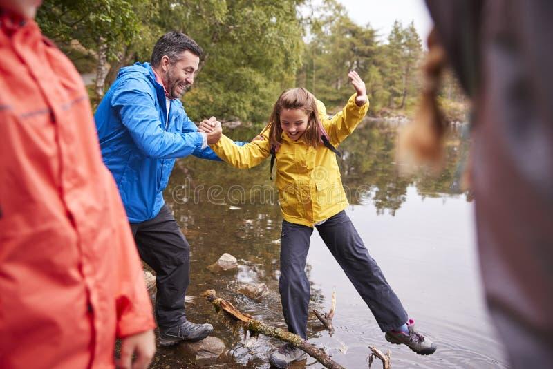 Mellersta åldrig fader som rymmer hans hand för daughterï¿ ½ s, medan hon balanserar på kusten området av för en sjö, sjön, UK fotografering för bildbyråer