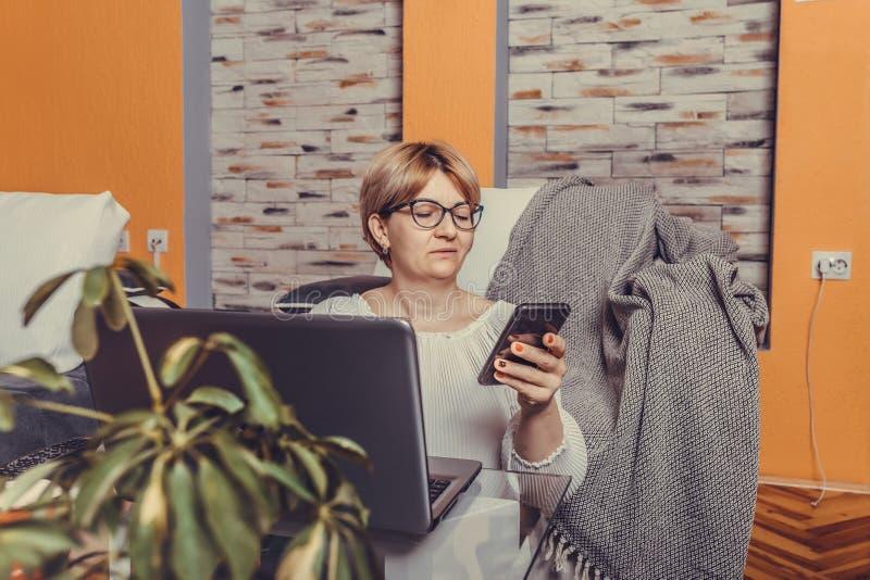 Mellersta åldrig kvinna som använder smartphonen och hemma arbetar på bärbara datorn royaltyfri fotografi