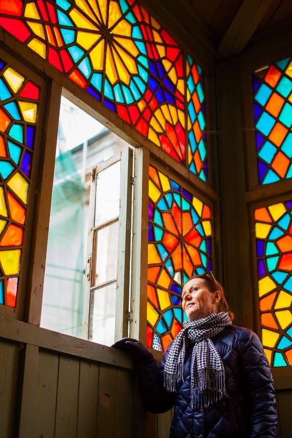 Mellersta åldrig kvinna som ser genom hela fönster med mång--färgad målat glass, gamla Tbilisi, Georgia, Januari 2019 royaltyfria bilder