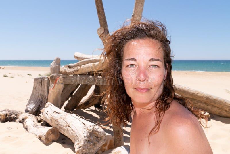 Mellersta åldrig semesterkvinna som sitter vid havet i sommarferier arkivfoton