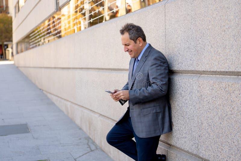 Mellersta åldrig stilig affärsman som använder mobiltelefonappen som överför meddelandet utanför kontor i stads- stad royaltyfria foton