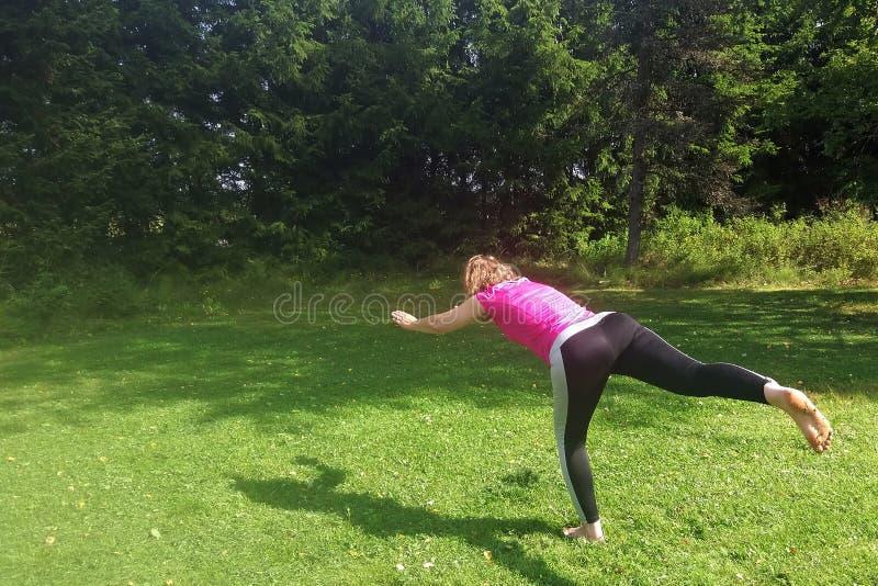 Mellersta åldrig yoga för yogakvinnaövning utomhus royaltyfria foton