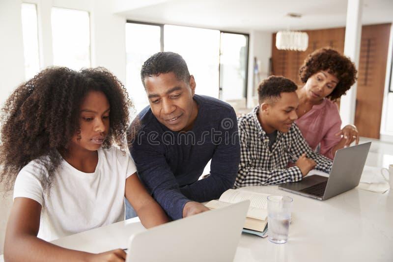 Mellersta åldriga afrikansk amerikanföräldrar som hjälper deras tonårs- ungar som använder bärbara datorer för att göra upp läxa, arkivfoto
