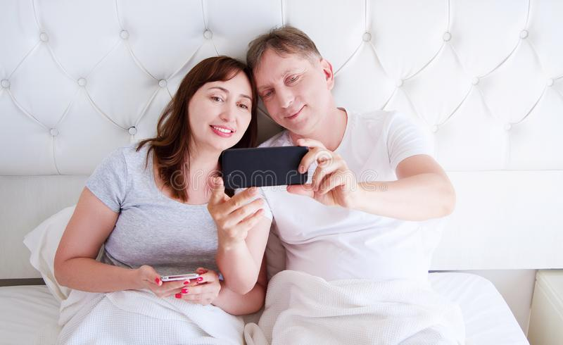 Mellersta åldriga par som ler och att göra selfie eller meddela på smartphonen i sovrummet, lycklig familj royaltyfri fotografi