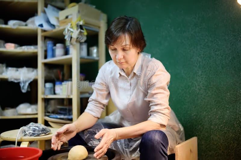 Mellersta objekt för lera för ålderkvinnadanande Skulptören under arbete i krukmakeriseminarium arkivbild