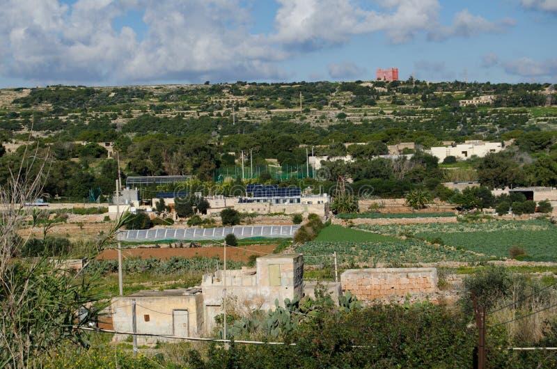 Mellieha, Мальта - 30-ое декабря 2018 - панели солнечных батарей на доме в середине полей земледелия под красной башней стоковое изображение rf