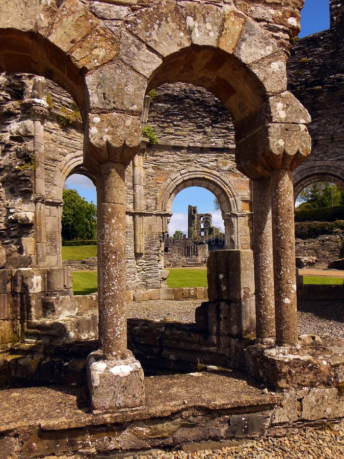 Mellifont Abbey, County Louth, Ireland. Peek-a-boo view through the ruins of Mellifont Abbey with the stone arches of the octagonal Lavabo in the foreground royalty free stock photography
