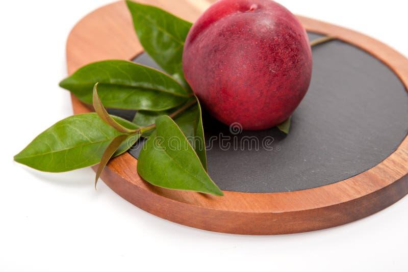 Melocotón recientemente lavado en la tabla de cortar de madera aislada en blanco fotografía de archivo