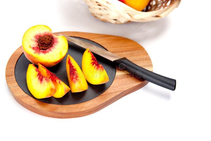 Melocotón recientemente lavado en tabla de cortar de madera con el cuchillo foto de archivo libre de regalías