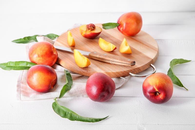 Melocotones dulces frescos con el tablero de madera en la tabla blanca foto de archivo libre de regalías