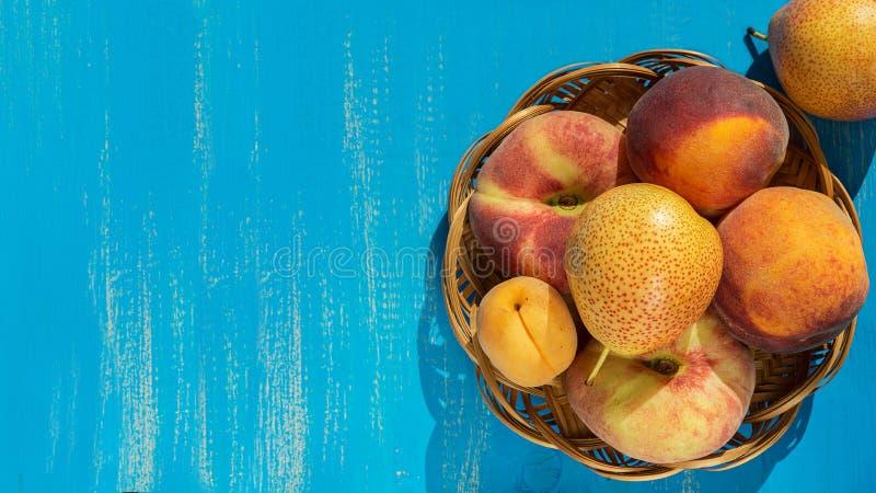 Melocotones, peras y albaricoques maduros frescos en una placa en un fondo de madera azul Fondo de la fruta fresca Frutas del ver imagenes de archivo