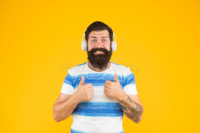 Melody for relax. Man bearded hipster with mustache long beard listening song headphones yellow background. Summer. Playlist. Music for summer vacation. Guy royalty free stock photo