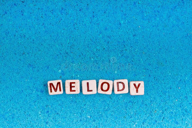 Melody word on stone. Melody word write in square white stone on blue sand, free space for your text royalty free stock photography