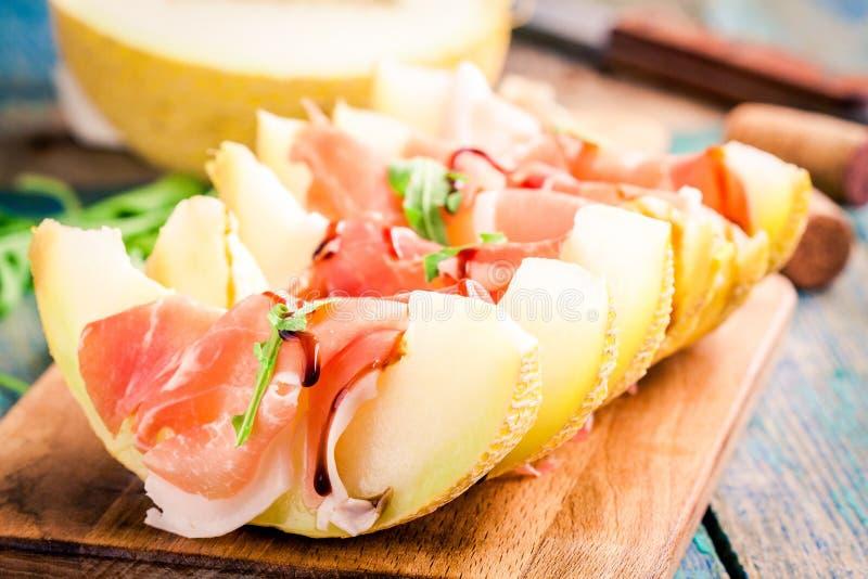 Meloen met dunne plakken van prosciutto en arugulabladeren stock foto