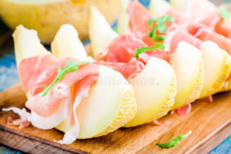 Meloen met dunne plakken van prosciutto en arugulabladeren royalty-vrije stock afbeelding