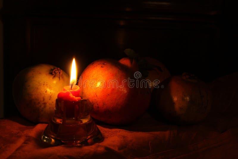 Melograni con la candela di raggiro di Melegrane della candela fotografia stock