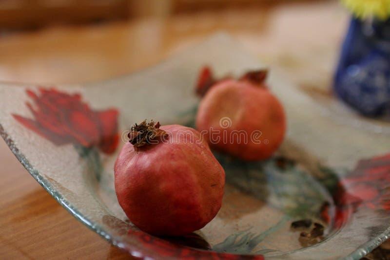 Melograni in una ciotola sul tavolo da pranzo fotografia stock