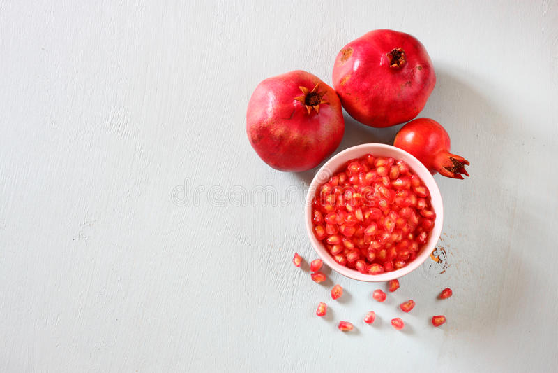 Melograno sulla tavola di legno e seme fresco del pomegrante in ciotola - vista superiore. fotografia stock