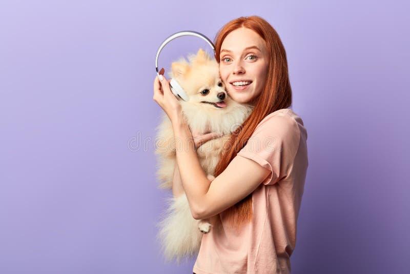 Melomanic-Hund und sein Eigentümer erhalten Vergnügen vom Hören Musik lizenzfreie stockbilder