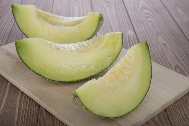 Melon coupé en tranches de cantaloup de melon de cantaloup dessus sur la planche à découper en bois et le fond en bois photo libre de droits
