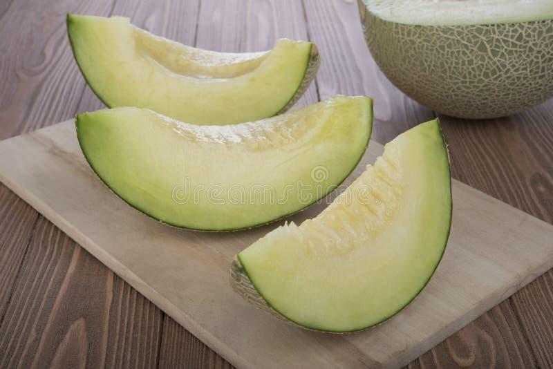 Melon coupé en tranches de cantaloup et demi melon de cantaloup dessus sur la planche à découper en bois et le fond en bois image stock