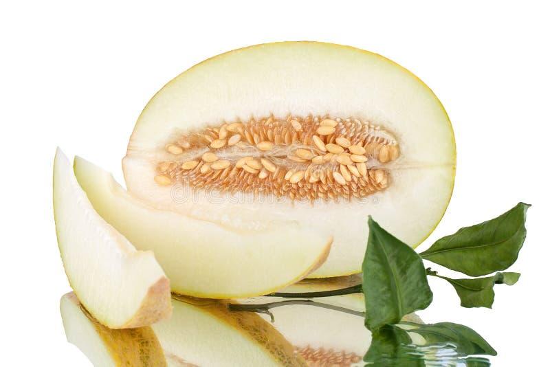 Melon coupé en tranches jaune avec des graines et des feuilles vertes sur le fond blanc de miroir d'isolement étroitement  photo libre de droits