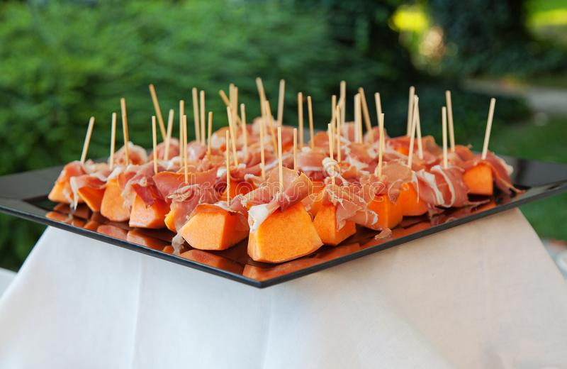 Melon cut into portionts and ham, served during a banquet stock photos