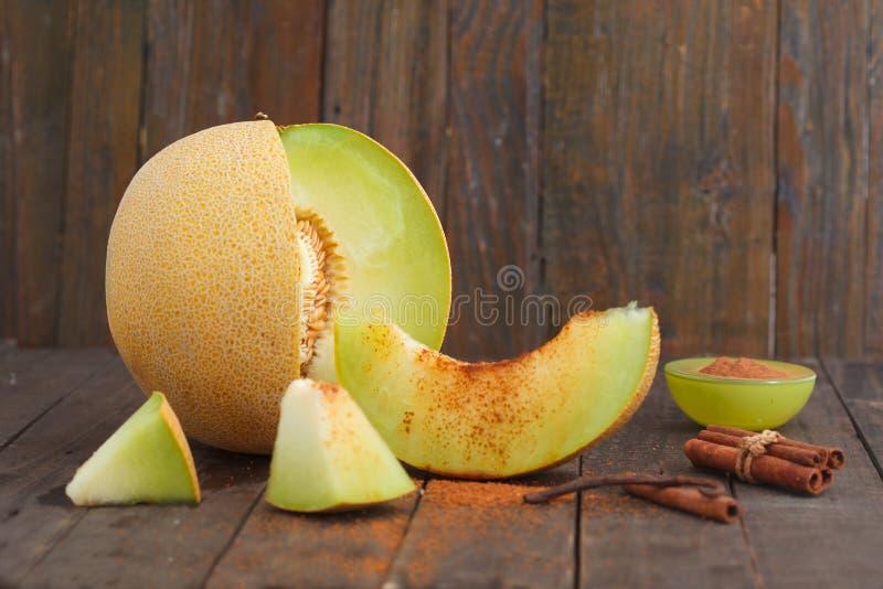 Melon de cantaloup et tranches de melon avec de la cannelle et le sucre roux sur le fond en bois photographie stock libre de droits
